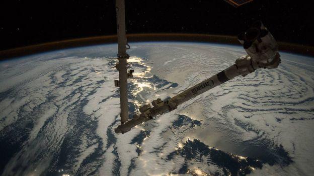 Imagem mostrando um braço mecânico no espaço, sobre a atmosfera da Terra