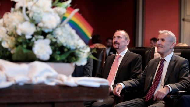 Karl Kreil and Bodo Mende sit in front of a table with flowers and rainbow flags