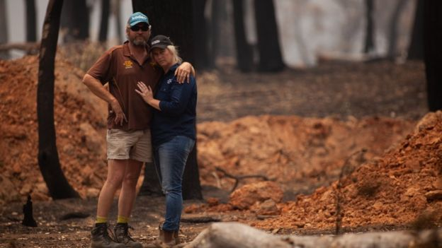 Travis and Belinda Attree cling to each other as they assess their scorched land