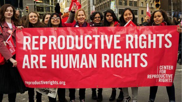 """Un grupo de mujeres sujeta una pancarta que lee: """"Los derechos reproductivos son derechos humanos"""""""