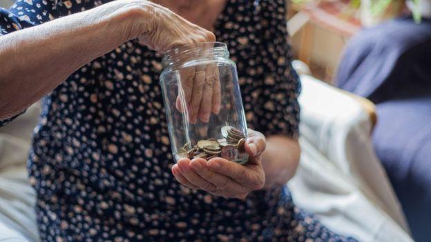 Adulta mayor introduce una mano en un frasco con monedas