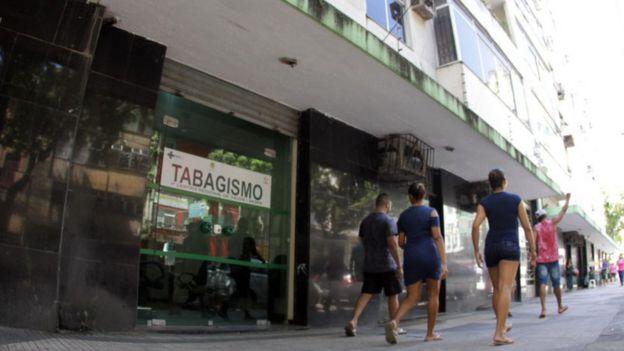 Pedestres caminham em frente a porta com cartaz de serviço de saúde com a palavra TABAGISMO destacada