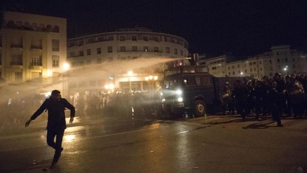 A Moroccan protester runs as the police use a water cannon during a demonstration in the capital Rabat on 24 March 2019