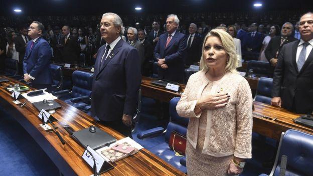 Selma Arruda aparece com a mão no peito, enquanto é executado o Hino Nacional, ao lado de outros parlamentares enfileirados