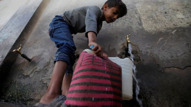 A boy fills canisters with water at a public tap in Sanaa, Yemen (13 October 2017)