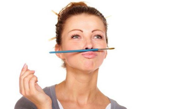 Una mujer que mira al horizonte, con un lápiz entre el labio superior y la nariz