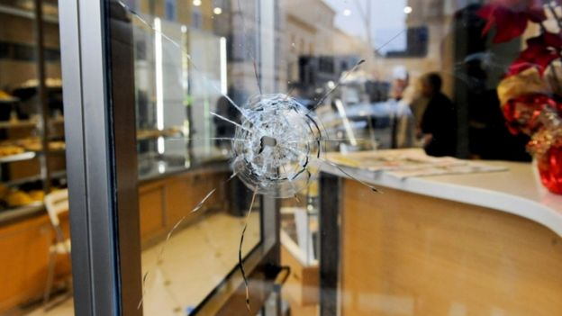 A bullet hole in a shop window as police investigate the shooting of foreign nationals at Macerata, 3 February 2018