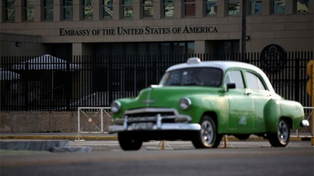 A green car driving past the US embassy in Havana
