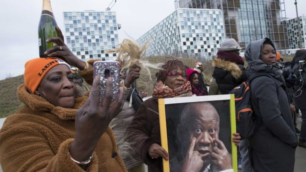 Supporters of Laurent Gbagbo rally outside the ICC, holding up a photo of him and a bottle of champagne