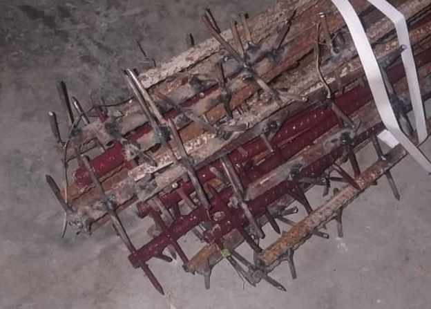 An image showing iron rods studded with nails