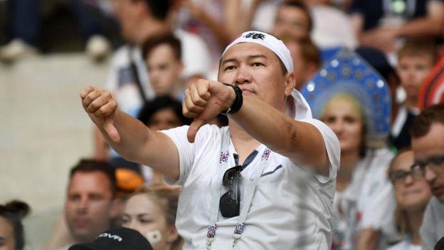Un aficionado japonés hace una señal con los pulgares hacia abajo durante el partido de Japón y Polonia en Rusia 2018