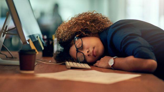 Una trabajadora estadounidense dormida en su escritorio.