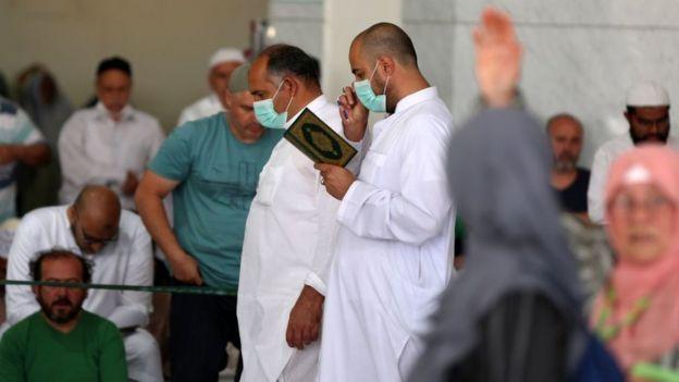 Umat Islam menggunakan masker saat Sholat Jumat di depan Masjid Agung Makkah.