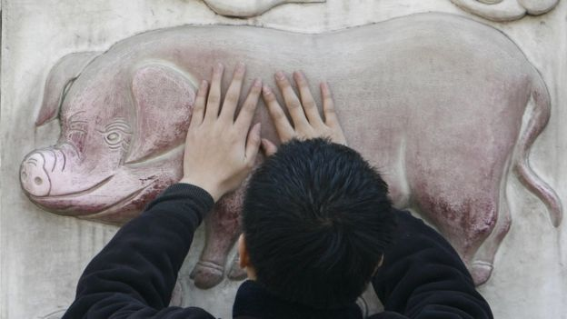 A man rubs his hands on a sculpture of a pig for good luck