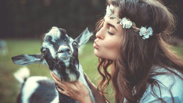 Девушка на природе пытается поцеловать козу