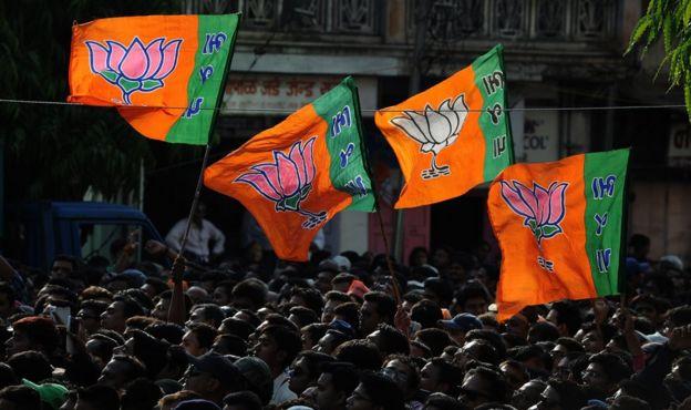 Сторонники Бхараты Джаната (BJP) поддерживают флаги во время общественного митинга кандидатом на пост премьер-министра BJP Нарендры Моди после его победы в Вадодаре 16 мая 2014 года.