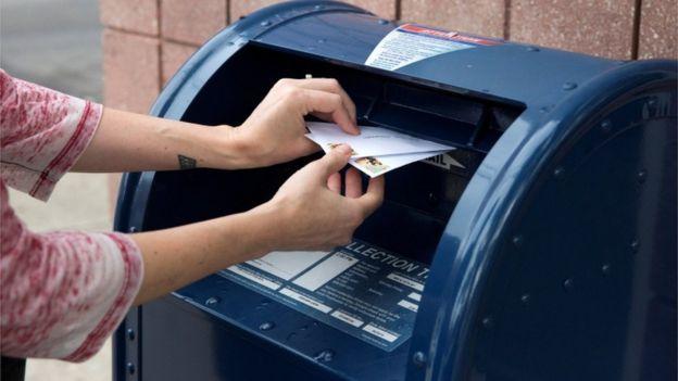 Una mujer deposita cartas