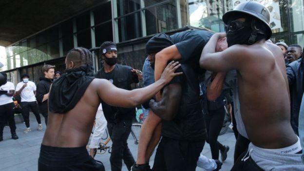 Patrick Hutchinson y sus amigos protegiendo a un manifestante