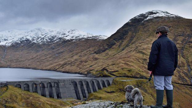 Varón en la montaña frente a una presa.