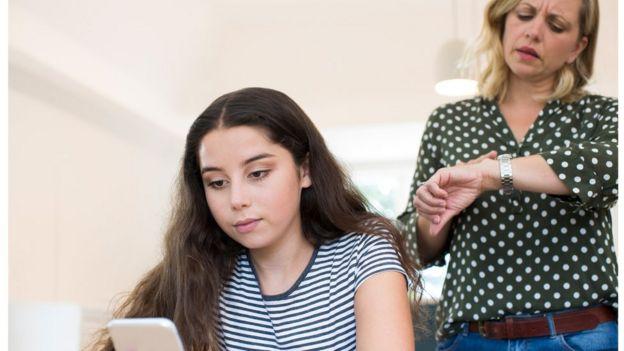 Adolescente sentada usa celular e mãe aparece atrás com olhar preocupado e olhando o relógio