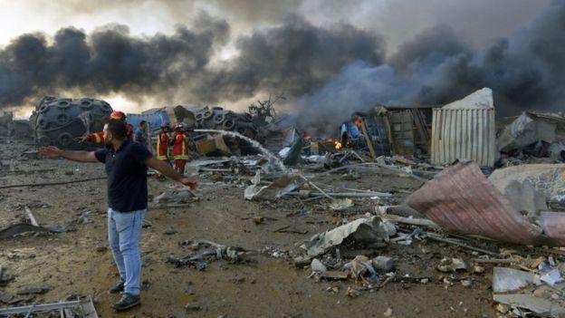 Homens e agentes de segurança trabalham em área devastada por explosão