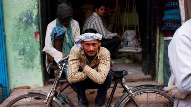 Un joven sentado afuera de un taller.