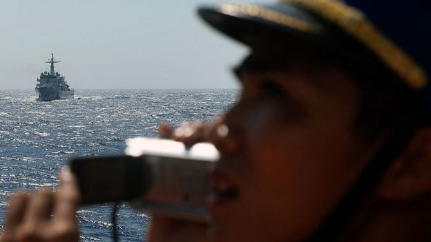 This picture taken from a Vietnam Coast Guard ship on May 14, 2014 shows a Vietnamese Coast Guard officer taking picture of a China Coast Guard ship