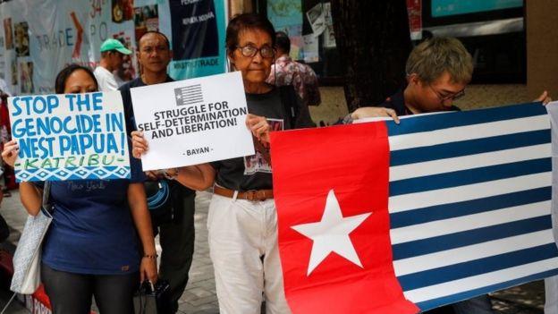 Manifestantes protestan en solidaridad frente a la embajada de Indonesia, en Manila, Filipinas. Uno enarbola la bandera de la Estrella del Amanecer.