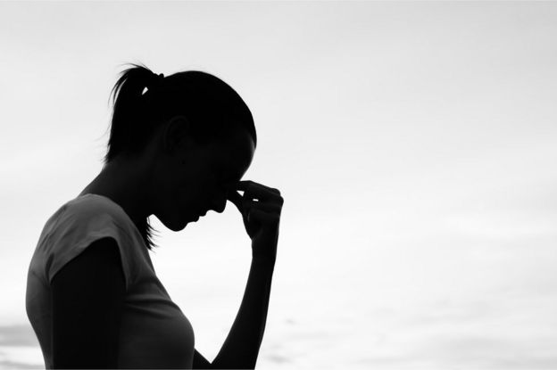 Silhouette of a woman holding her head