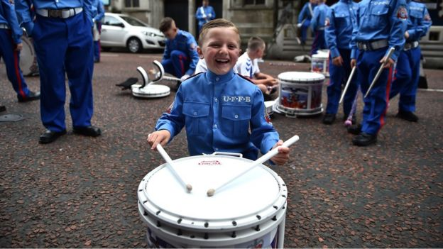 A young boy in a band uniform smiles as he plays a drum