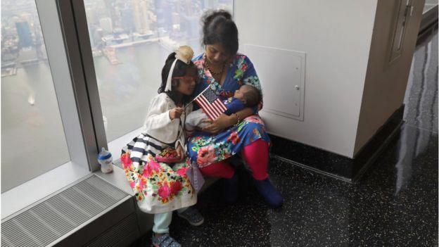 一名孟加拉移民与孩子参加了一个入籍美国仪式。她的孩子手里举着一面美国国旗。