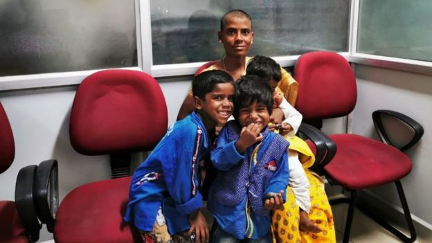 Prema with her kids waiting to meet a government official