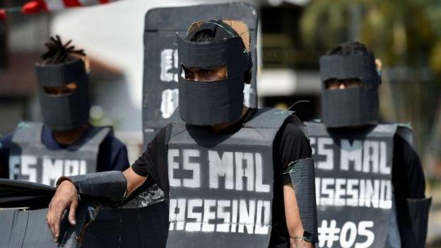 Estudiantes universitarios disfrazados de miembros del Escuadrón Antidisturbios Móvil (Esmad), se manifiestan durante una protesta contra el gobierno del presidente colombiano Ivan Duque en Cali, Colombia, el 4 de diciembre de 2019.