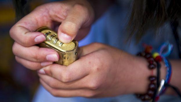 Niño tratando de abrir un candado