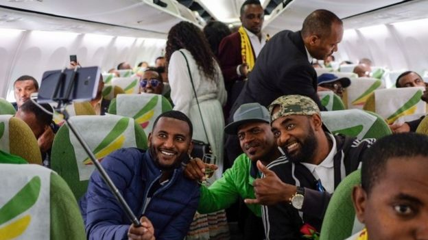 """Passengers pose for a selfie picture inside an Ethiopian Airlines flight who departed from the Bole International Airport in Addis Ababa, Ethiopia, to Eritrea""""s capital Asmara on July 18, 2018"""