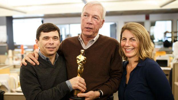 The Boston Globe's Michael Rezendes, left, Walter V. Robinson, and Sascha Pfieffer, right, hold Oscar winning writer Josh Singer's Oscar statue in the newsroom of the Boston Globe