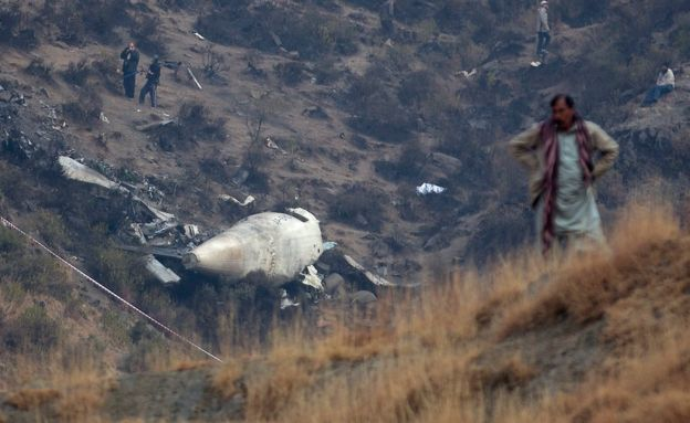 A villager stands at a site overlooking the site of plane crash, in Gugh, near Havelian, Pakistan, 8 December 2016.