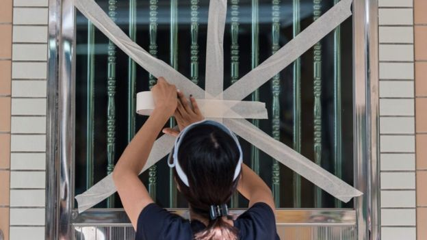 A resident of a fishing village in Hong Kong tapes up her windows