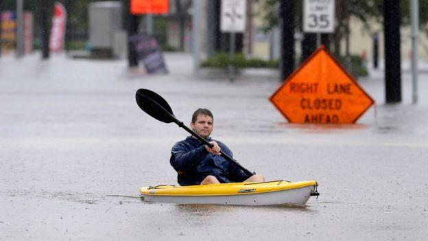 Un hombre trasladándose en canoa en un camino el norte de Houston.