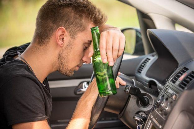 Joven con botella de cerveza en la mano apoyado sobre el volante del coche.