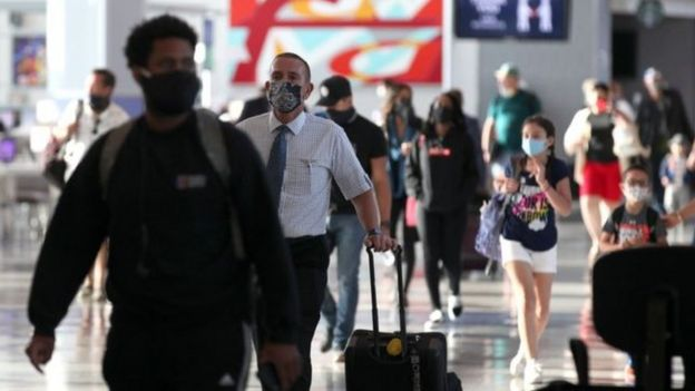 Travellers wearing face masks in an airport