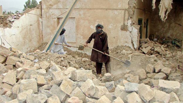 Locais demovem destroços de um edifício destruído por um drone americano no Paquistão