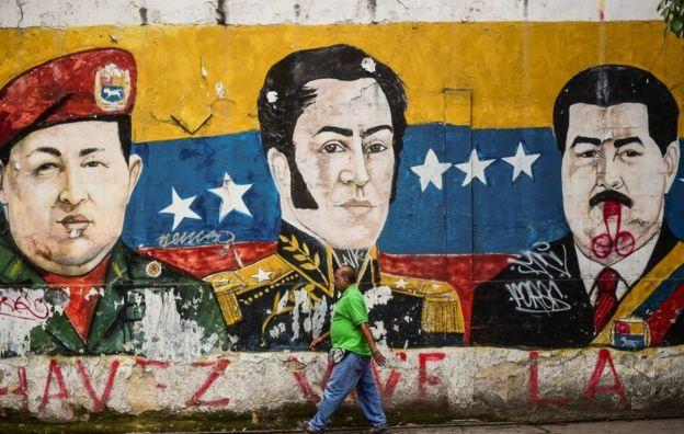 Hombre pasa frente a un mural de Hugo Chávez, Simón Bolívar y Nicolás Maduro en Caracas, Venezuela.
