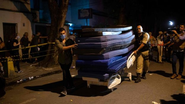 Men carry mats to ambulances transferring patients during a fire at the Badim private Hospital in Tijuca neighborhood, Rio de Janeiro, Brazil, on September 12, 2019