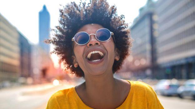 Mujer sonriente bajo un día soleado.