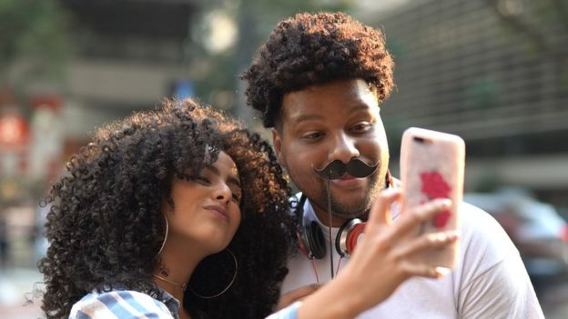 A young couple taking a selfie, they are using a moustache prop