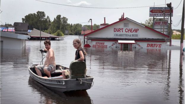 Residents use a boat to get back to a home as floodwater from the Mississippi River continues to rise