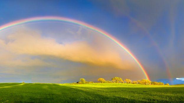 Um arco-íris duplo sobre um céu azul