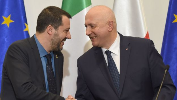 Matteo Salvini, left, smiles and shakes hands with Joachim Brudzinski at a press conference event - behind the pair are both nation's flags and the flag of the EU