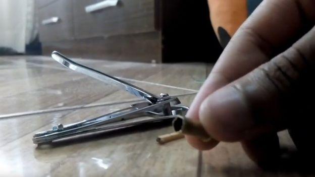 Cortador de unha, palito de fósforo e mão de instrutor com finca pino